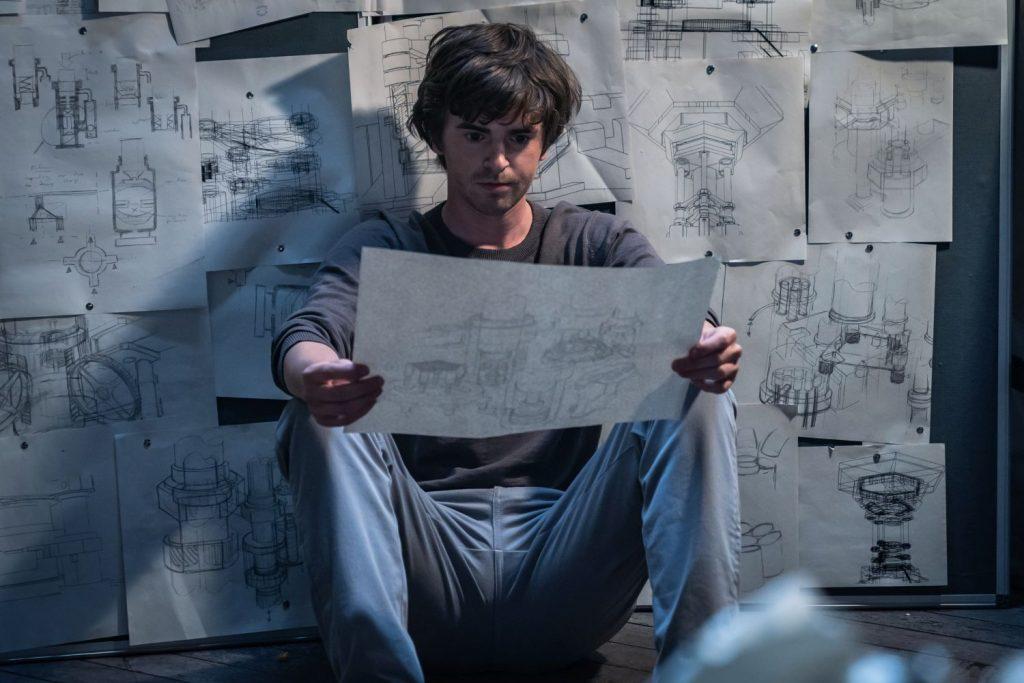 Ein junger Mann schaut nachdenklich aus eine technische Zeichnung. Hinter ihm hängen viele solche Zeichnungen an der Wand.