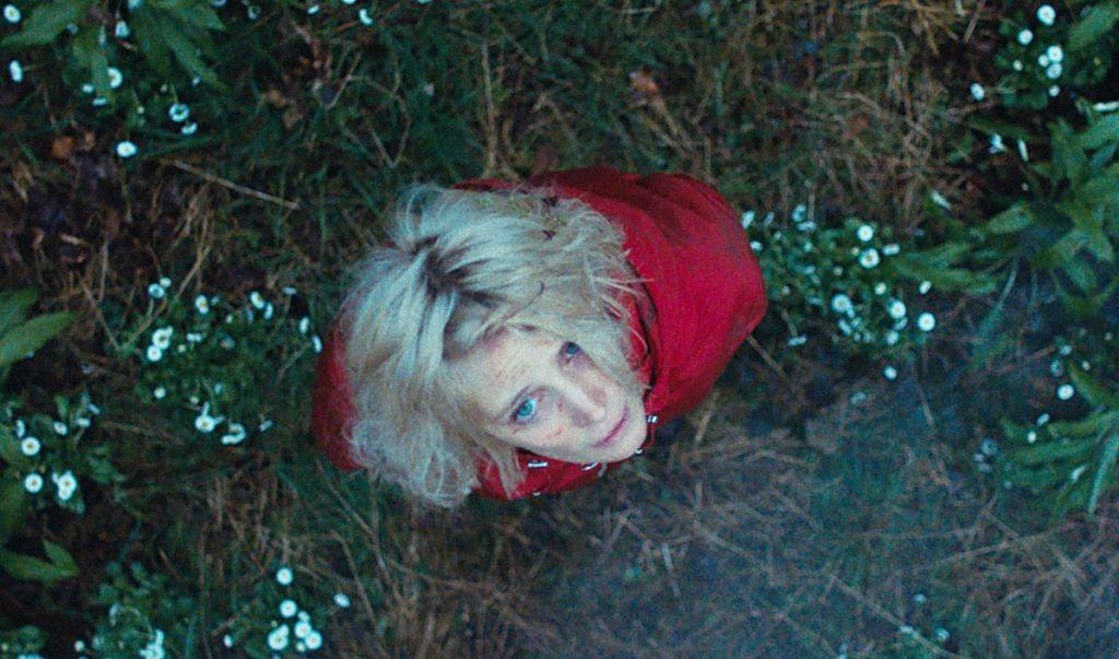 Eine Frau in roter Jacke steht auf einer Wiese mit Gänseblümchen. Sie ist von oben zu sehen und schaut in die Kamera.