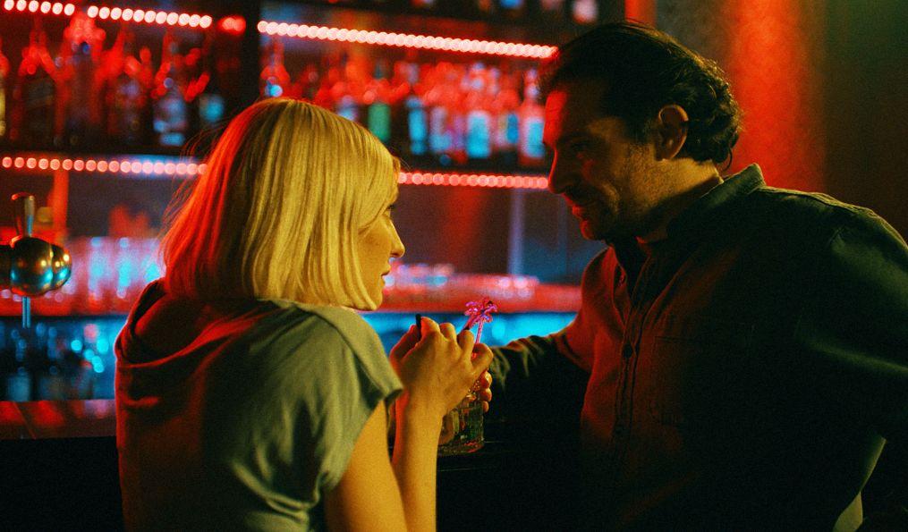 Eine Frau und ein Mann in einer Bar. Sie sieht ihn an, er lächelt.