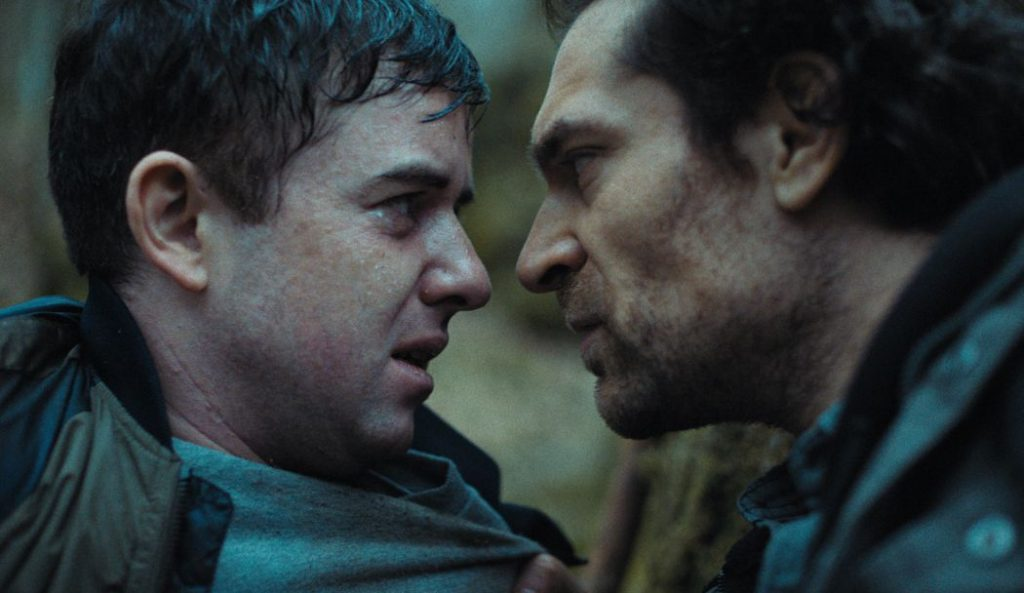 Zwei Männer schauen sich an, der eine ängstlich, der andere aggressiv.
