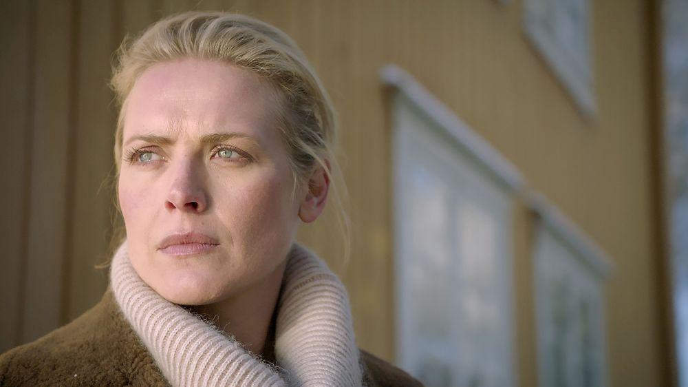 Eine blonde Frau vor einem Holzhaus. Sie schaut nachdenklich in die Ferne.