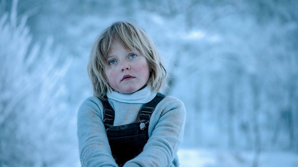 Ein kleines blondes Mädchen in eiskalter Winterlandschaft.