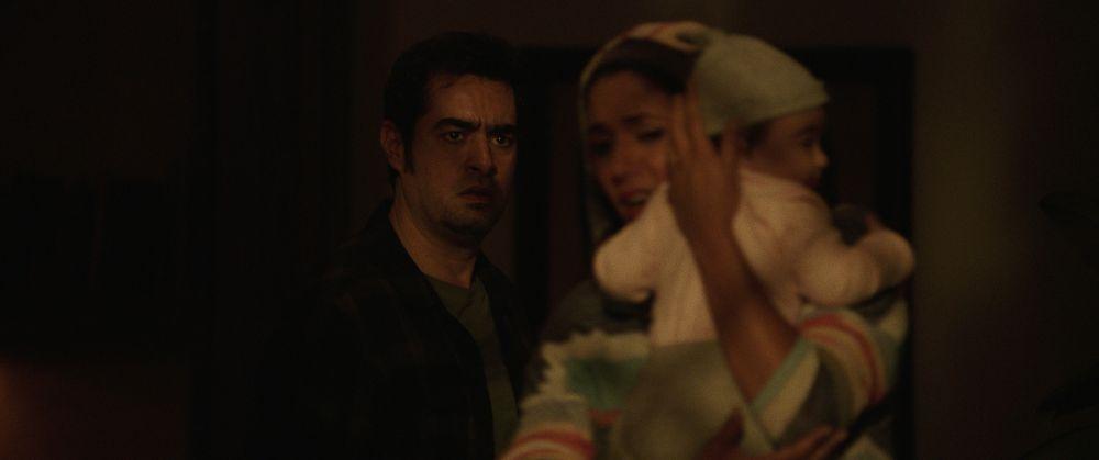 Ein Mann und eine Frau im Haldunke, sie hält ein Baby. Er blickt entsetzt, sie weit.