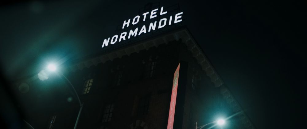 Im Dinkeln leuchtende Schriftzüge: Hotel Normandie.