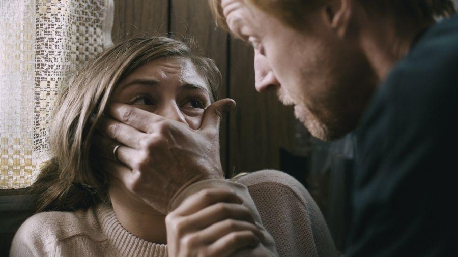 Ein Mann hält einer schockiert blickenden Frau den Mund zu.