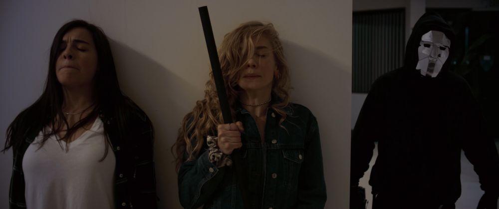 Zwei junge Frauen verstecken sich hinter einer Ecke, während rechts ein Mann mit spiegelnder Maske näher kommt.