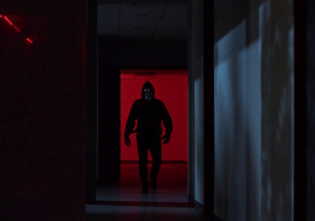 Ein Mann in dunkler Kleidung und spiegelnder Maske kommt einen Gang herunter.