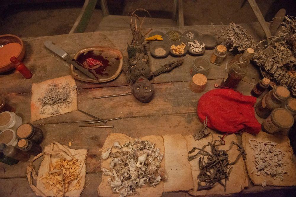 Auf einem Tisch liegen okkulte Materialien wie Muscheln, Samen, Kräuter, Nägel und eine Puppe.