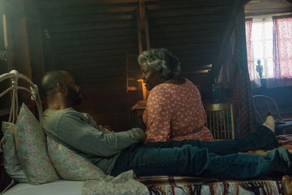 Ein Mann liegt auf einem Bett. Bei ihm sitzt eine ältere Frau.